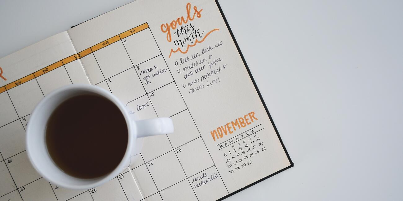 Coffee cup on top of calendar and goal list