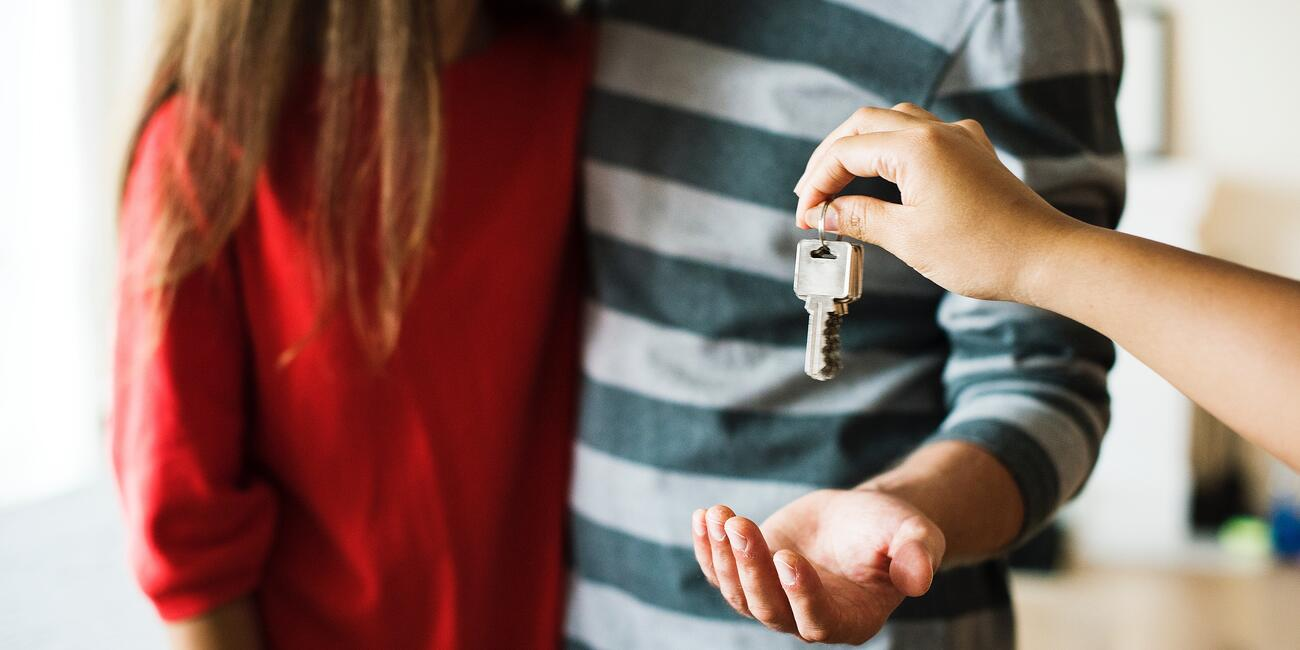 House key being dropped into hand of young person