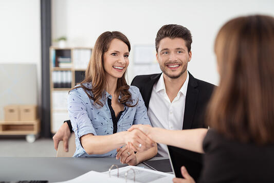 Happy Young Professional Couple Shaking Hands with a Real Estate Agent After Some Business Discussions Inside the Office.