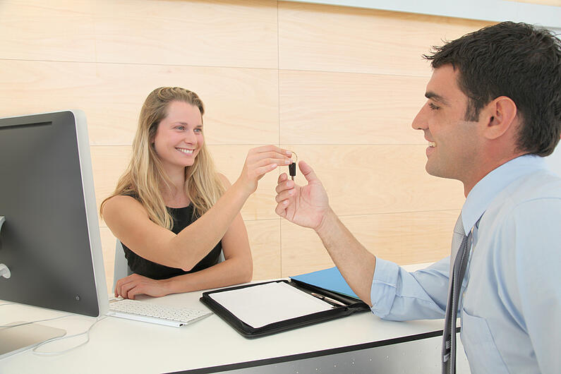 Woman giving car key to businessman